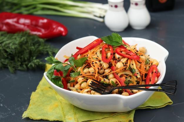 Insalata sana di ceci, carote coreane, peperoni e cipolle decorata con sesamo nero Foto Premium