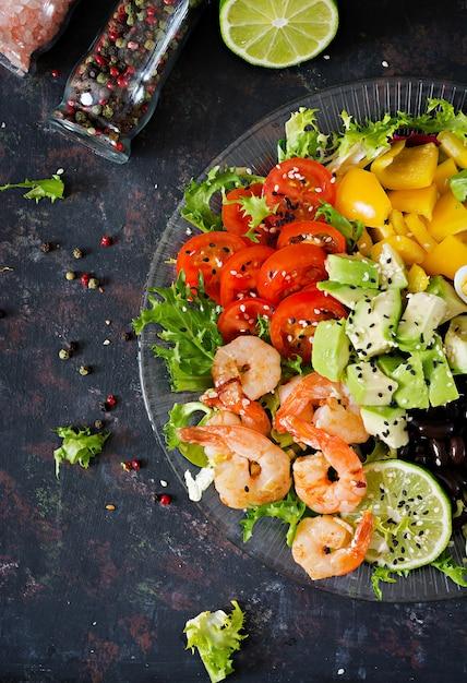 Insalata sana. ricetta di pesce fresco. gamberi alla griglia e insalata di verdure fresche - avocado, pomodoro, fagioli neri, cavolo rosso e paprika. gamberi alla griglia. cibo salutare. disteso. Foto Premium