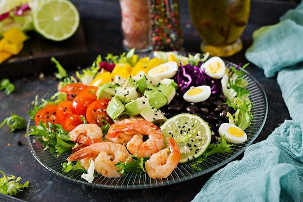 Insalata sana. ricetta di pesce fresco. gamberi alla griglia e insalata di verdure fresche - avocado, pomodoro, fagioli neri, cavolo rosso e paprika. gamberi alla griglia. cibo salutare. Foto Premium