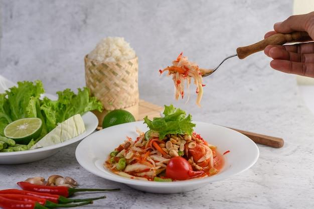 Insalata tailandese della papaia in un piatto bianco con riso appiccicoso e gamberetti essiccati Foto Gratuite