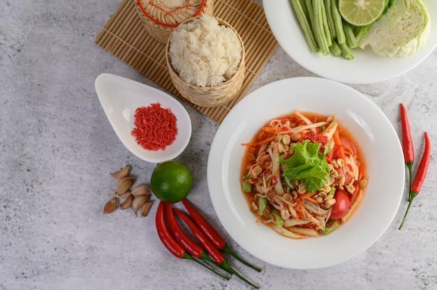 Insalata tailandese della papaia in un piatto bianco con riso appiccicoso in bambù del canestro di vimini e gamberetto essiccato Foto Gratuite