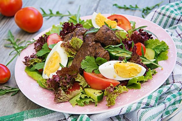 Insalata tiepida di fegato di pollo, pomodoro, cetriolo e uova. cena salutare. menu dietetico Foto Gratuite