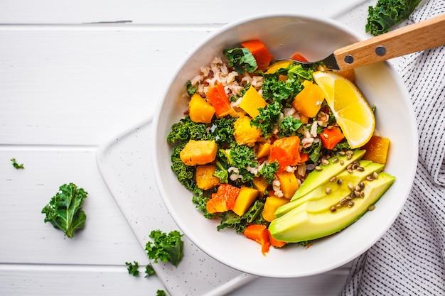 Insalata vegana con riso, cavolo, zucca al forno, carote e avocado Foto Premium