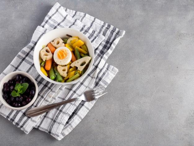 Insalata vegetariana con frutti di bosco sul tavolo grigio Foto Gratuite