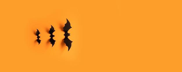 Insegna di halloween con i pipistrelli neri su una superficie arancio, vista superiore. Foto Premium
