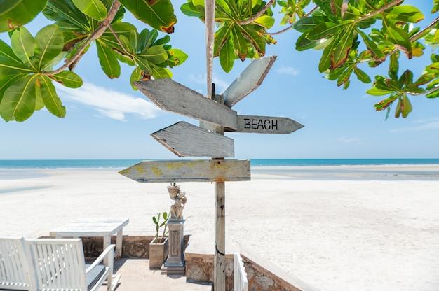 Insegna di legno delle frecce sulla spiaggia con la pianta verde Foto Premium