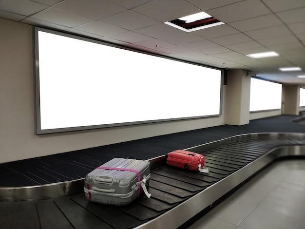 Insegna in bianco del manifesto sopra l'esposizione della cinghia dei bagagli. tabellone per le affissioni bianco per l'annuncio di promozione e le informazioni di pubblicità di affari deridono. Foto Premium