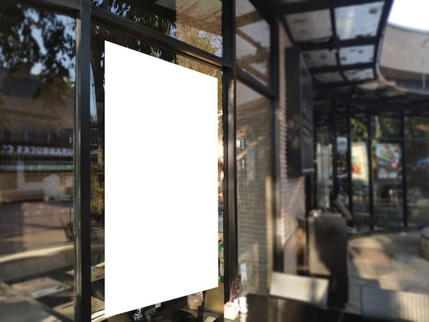 Insegna in bianco del manifesto su vetro all'esposizione del ristorante tabellone per le affissioni bianco per l'annuncio di promozione e le informazioni di pubblicità di affari deridono su. Foto Premium
