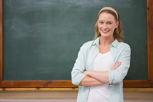 Insegnante che sorride alla macchina fotografica con le braccia attraversate Foto Premium