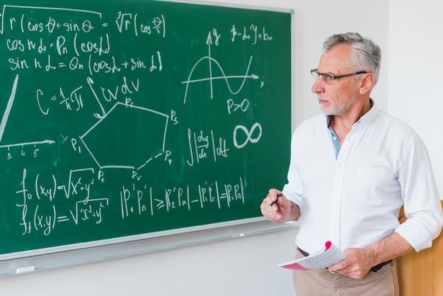 Insegnante di matematica invecchiato accanto alla lavagna Foto Gratuite