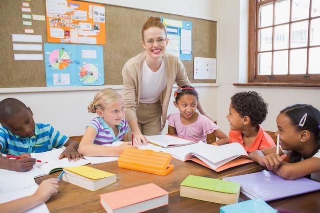 Insegnante grazioso che aiuta gli allievi in aula Foto Premium