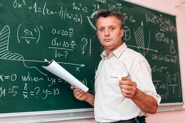 Insegnante in piedi accanto a una lavagna e spiegare una lezione in possesso di un libro di testo. Foto Premium