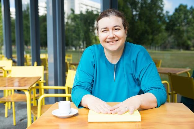Insegnante positivo che beve caffè al college cafe Foto Gratuite