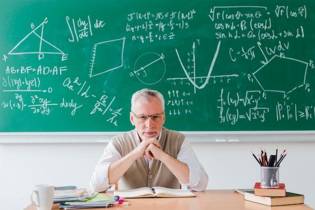 Insegnante rigoroso che guarda l'obbiettivo in aula Foto Gratuite