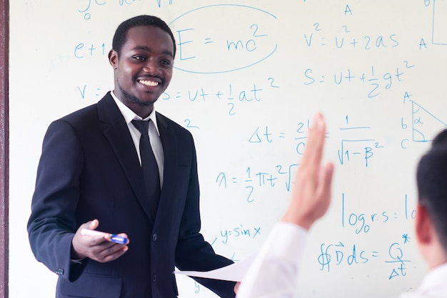 Insegnante straniera africana che insegna scienze in classe. Foto Premium