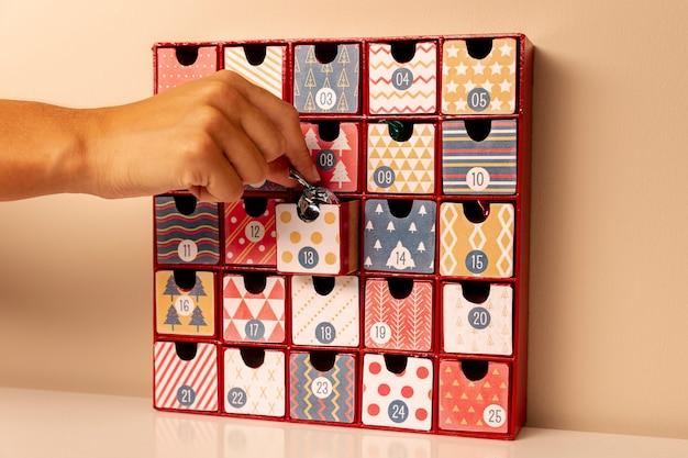 Inserimento manuale di piccole caramelle nel calendario dell'avvento Foto Gratuite
