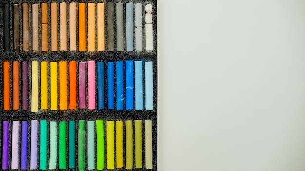 Insieme dei pastelli pastelli multicolori nella scatola di openartist su un fondo bianco, vista superiore. Foto Premium