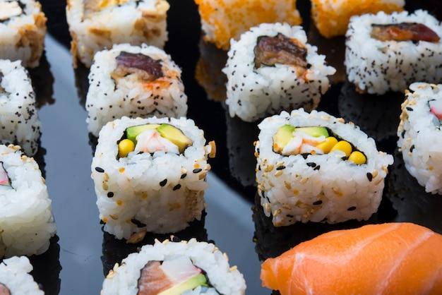 Insieme dei sushi isolato su fondo nero Foto Premium