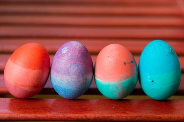 Insieme delle uova di pasqua che stanno sul fondo rosso della sedia. colorate uova luminose festive astratte dipinte di blu, rosa, verde e viola. Foto Premium