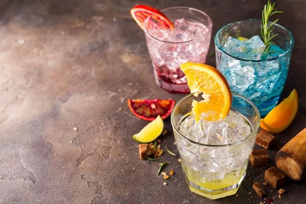Insieme di cocktail colorati con frutta ed erbe, zucchero di canna su priorità bassa di pietra Foto Premium