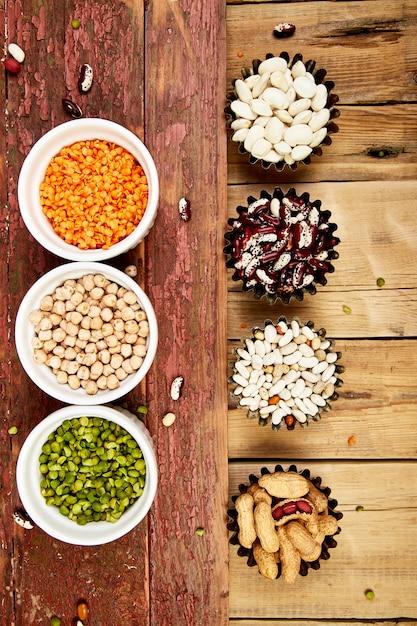 Insieme di raccolta di fagioli e legumi. ciotole di varie lenticchie Foto Premium