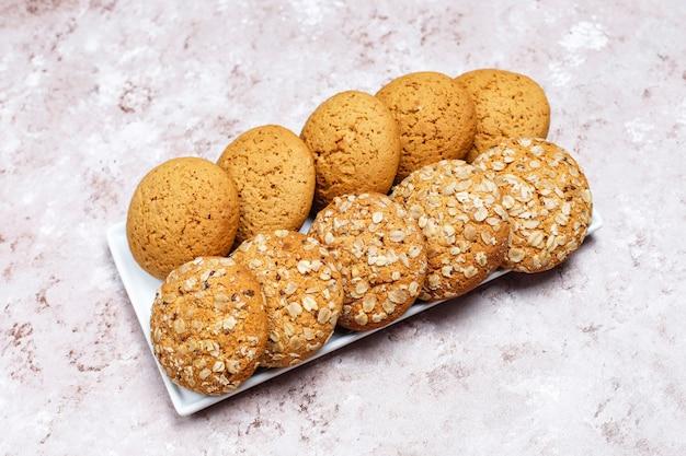 Insieme di vari biscotti in stile americano su uno sfondo di cemento chiaro. frollini con coriandoli, semi di sesamo, burro di arachidi, fiocchi d'avena e biscotti al cioccolato. Foto Gratuite