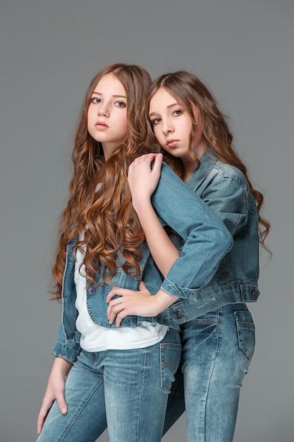 Integrale di giovane ragazza femminile esile in jeans del denim su fondo grigio Foto Gratuite