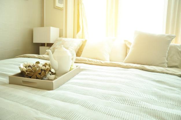 Interior design camera da letto con cuscini bianchi di lusso sul letto e lampada da tavolo decorativa. Foto Premium