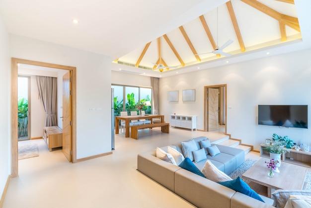 Interior design di lusso nel salotto di ville con piscina. spazio arioso e luminoso con alto soffitto alto e tavolo da pranzo in legno Foto Premium