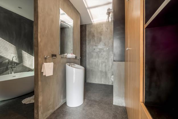 Interior design stile loft in bagno di lusso dispone di lavabo e vasca da bagno, servizi igienici in casa Foto Premium