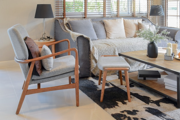 Interiore del salone con cuscini sul divano e tavolo in legno decorativo con lampada Foto Premium
