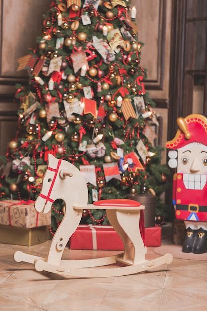 Interiore della decorazione della stanza di natale con la presidenza di cavallo, l'albero di nuovo anno e le schiaccianoci. Foto Premium