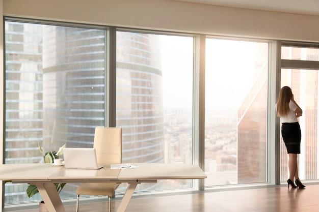 Interiore moderno dell'ufficio con la siluetta femminile che si leva in piedi alla finestra integrale Foto Gratuite