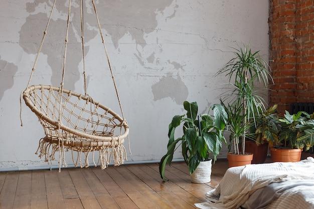 Interiore moderno della camera da letto con le piante da appartamento verdi e un'oscillazione Foto Premium