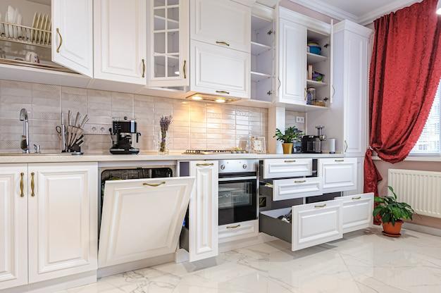 Interni di lusso in bianco moderno della cucina con ante e cassetti aperti Foto Premium