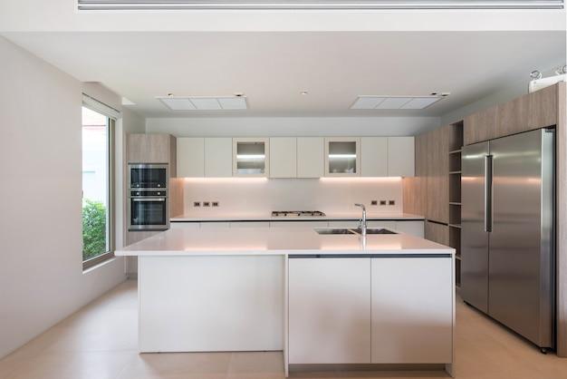 Interni di lusso nella zona cucina con bancone isola e mobili incorporati Foto Premium
