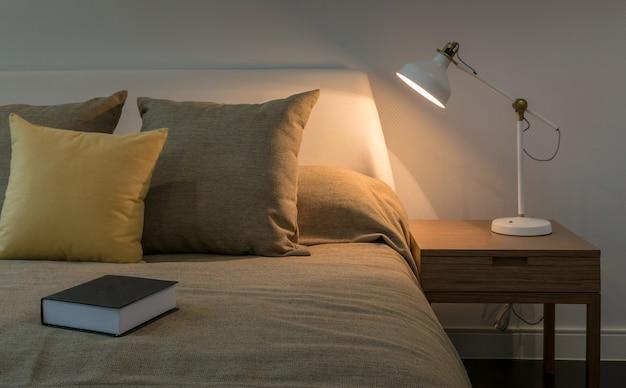 Interno accogliente della camera da letto con libro e lampada da lettura sul comodino Foto Premium