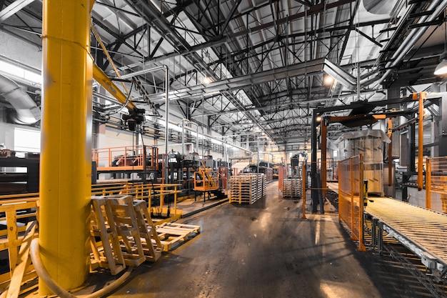 Interno dell'officina della fabbrica e macchine sulla parete di produzione di vetro Foto Premium