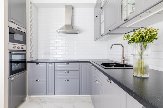 Interno della cucina moderna. piano di lavoro e lavandino scuri, frontali grigi dell'armadio. vaso con fiori decora la tavola Foto Premium
