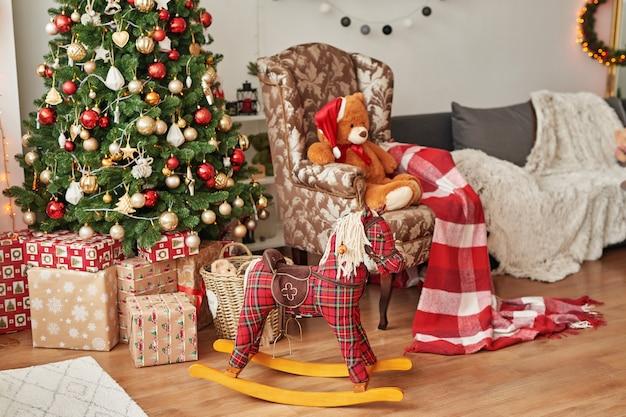 Interno di natale della cameretta dei bambini. il cavallo a dondolo e il giocattolo molle riguardano il fondo dell'albero di natale. Foto Premium