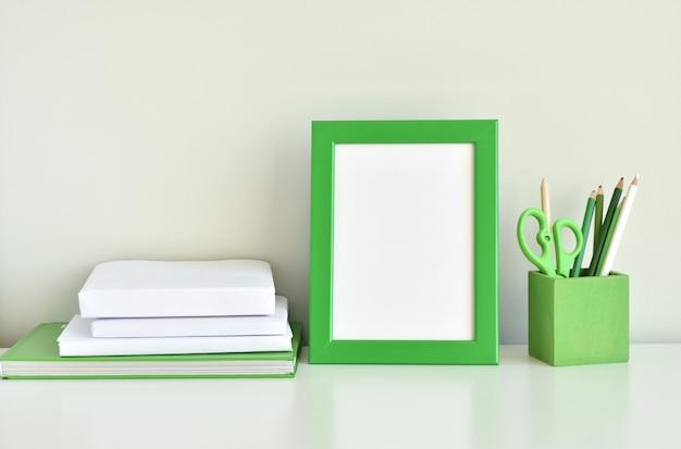 Interno verde della stanza dei bambini, modello della struttura della foto, libri, rifornimenti di scuola sulla tavola bianca. Foto Premium