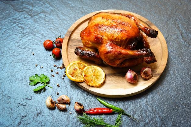 Intero pollo al forno con pollo arrostito grigliato con erbe e spezie sul piatto di legno e buio Foto Premium