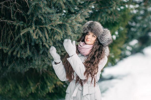 Inverno della ragazza beaty del cappello di pelliccia vicino all'abete rosso Foto Premium