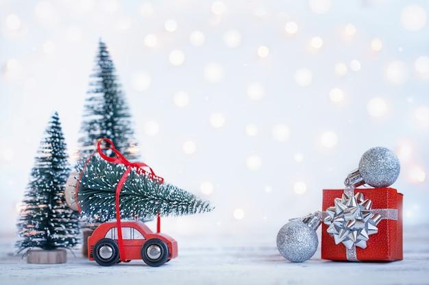 Inverno natale sfondo auto rossa in miniatura con abete. biglietto di auguri vacanze. Foto Premium