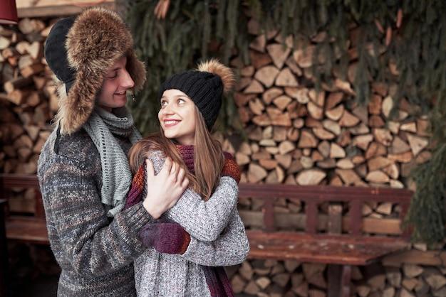Inverno, vacanze, coppia, natale e persone - uomo e donna sorridenti in cappelli e sciarpa che abbracciano sopra la casa di campagna e la neve di legno Foto Premium