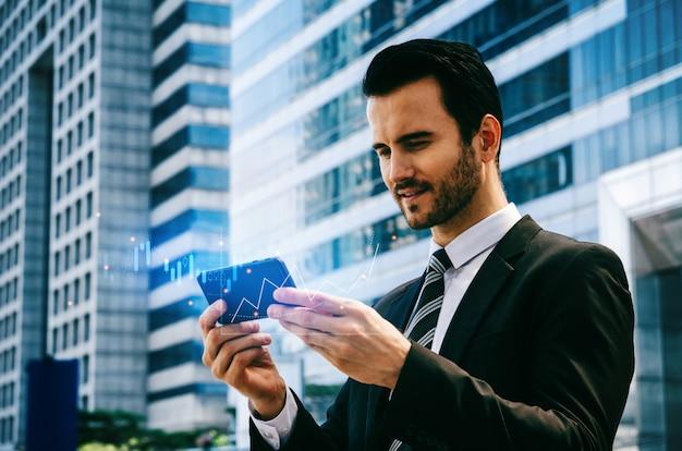 Investitore caucasico dell'uomo d'affari che utilizza i dati del mercato azionario di controllo del telefono cellulare con il grafico grafico del bastone della candela grafico dell'investimento del mercato azionario per il commercio di forex, rete internet, concetto di tecnologia Foto Premium