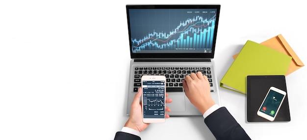 Investitore che analizza il mercato azionario finanziario. smartphone in mano e schermi di computer Foto Premium