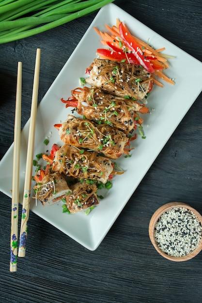 Involtini di petto di pollo al forno con erbe aromatiche, fette di carote, peperone su un tagliere scuro. stile asiatico. l'equilibrio di un'alimentazione sana. cucinando. tavolo in legno scuro. Foto Premium
