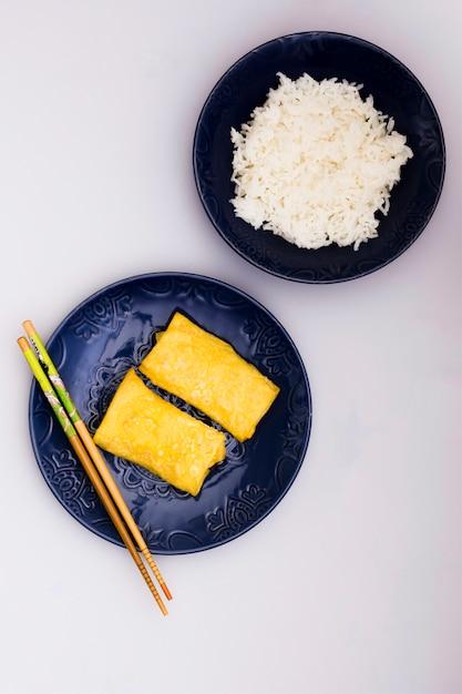 Involtini primavera fritti sul piatto con le bacchette vicino al semplice riso al vapore su sfondo bianco Foto Gratuite