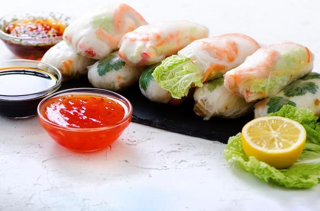Involtini primavera vietnamiti - carta di riso, lattuga, insalata, vermicelli, tagliatelle, gamberetti, salsa di pesce, peperoncino dolce, soia, limone, veletables Foto Premium
